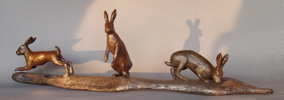 Three hare images in bronze